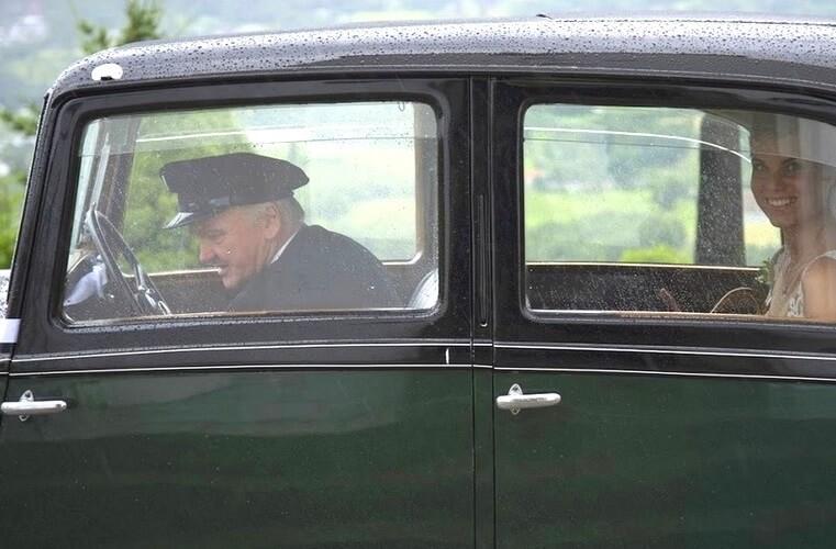 Flott gammel Rolls-Royce med brud som smiler fornøyd