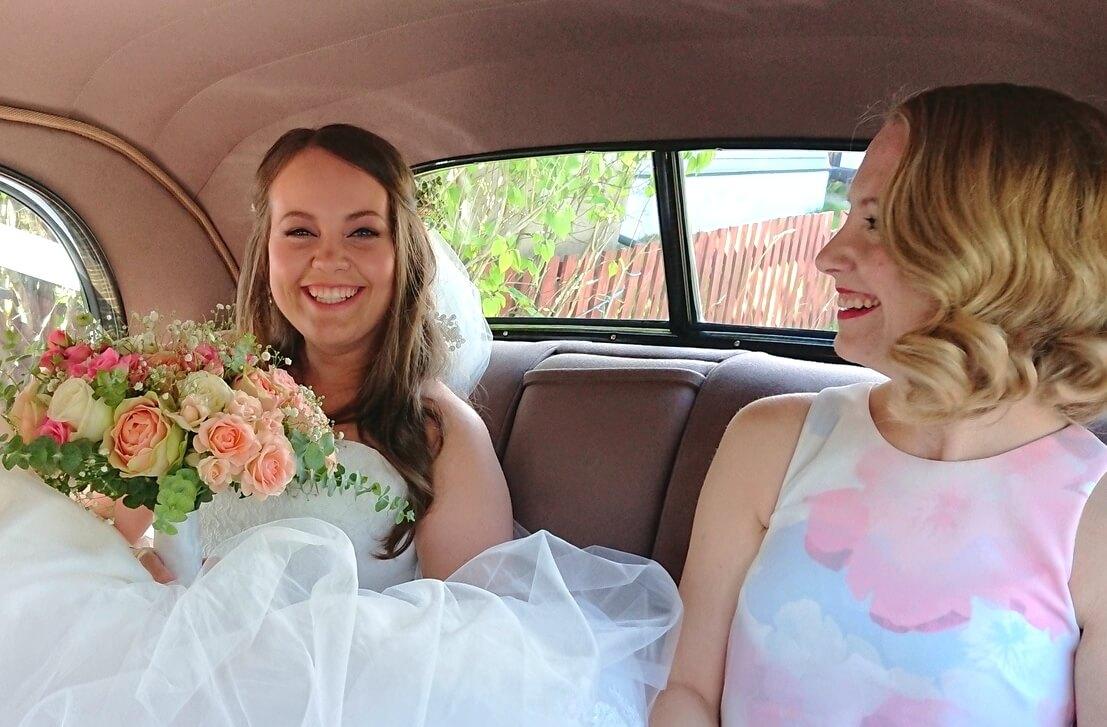 Brud og forlover i baksetet på en Buick veteranbil, klare for bryllup.