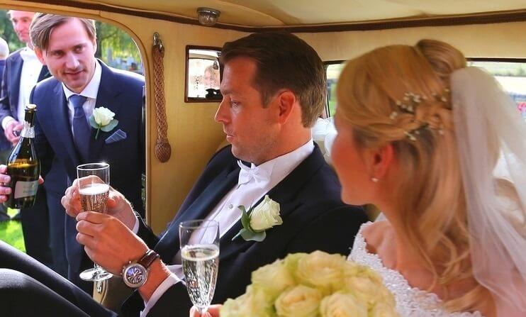 Forlover serverer Champagne til brudepar som sitter inne i bryllupsbilen. En Rolls-Royce Phantom fra 1930 tallet