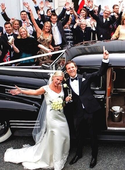Gjester og brudepar samlet rundt en sort Cadillac bryllupsbil og vinker