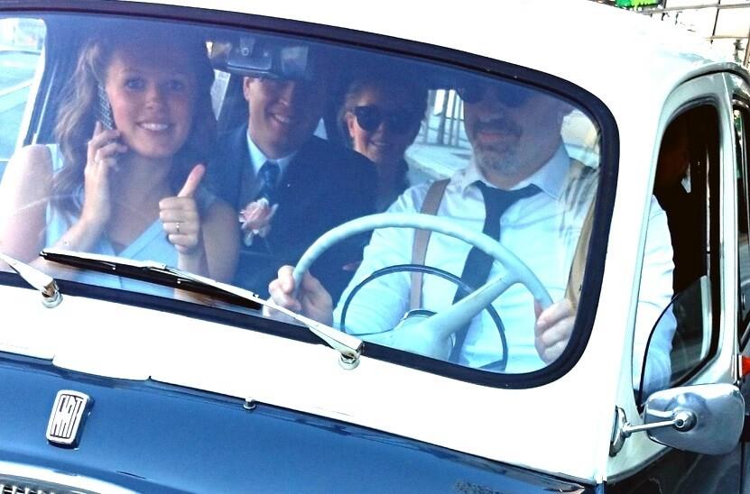 Liten Fiat veteranbil som bryllupsbil, stappfull av forlovere som smiler