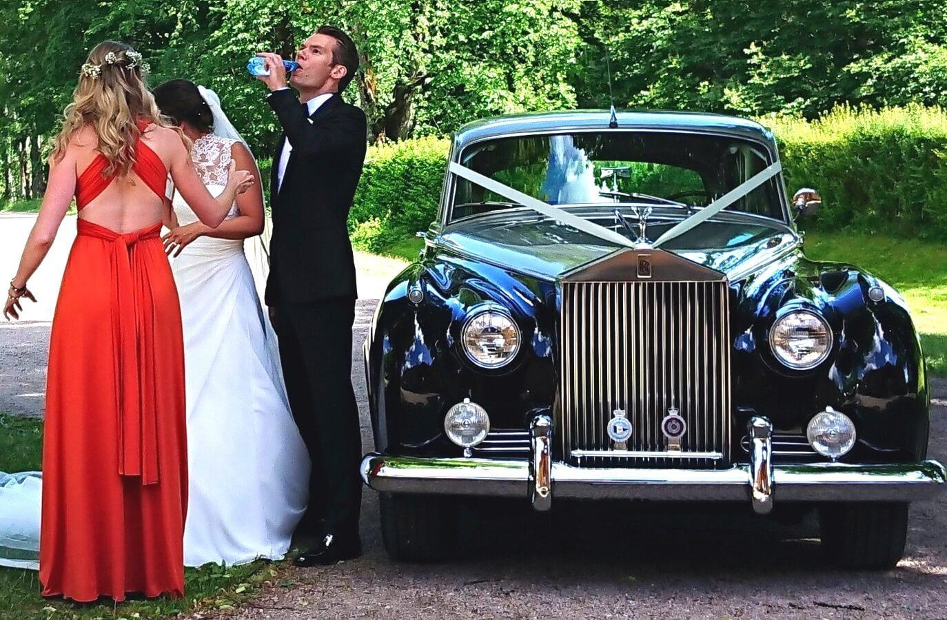 Pause for brudepar og forlovere i Oslo, ved siden av bryllupsbilen. En Rolls-Royce Silver Cloud