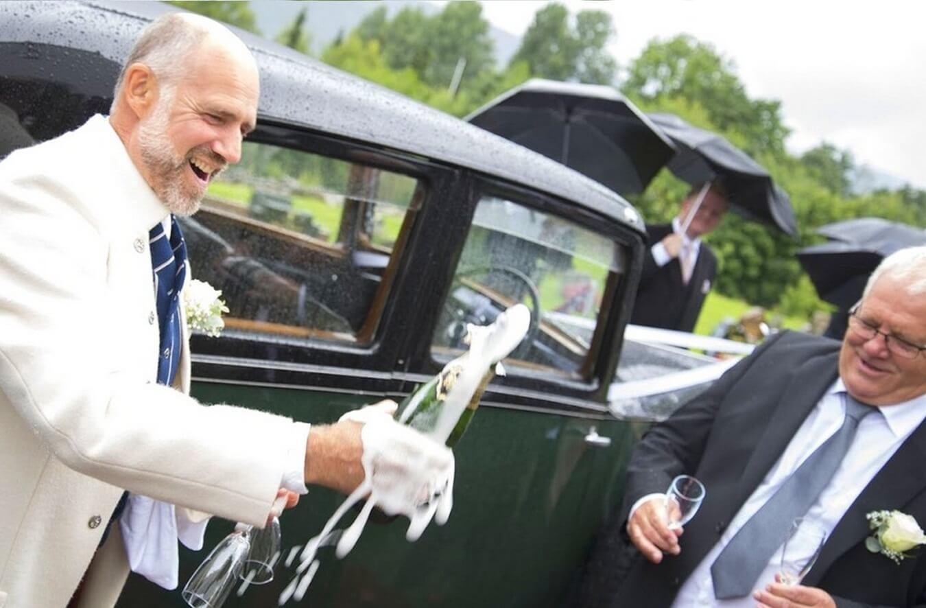 Glade menn med Champagne utenfor en flott vintage Rolls-Royce