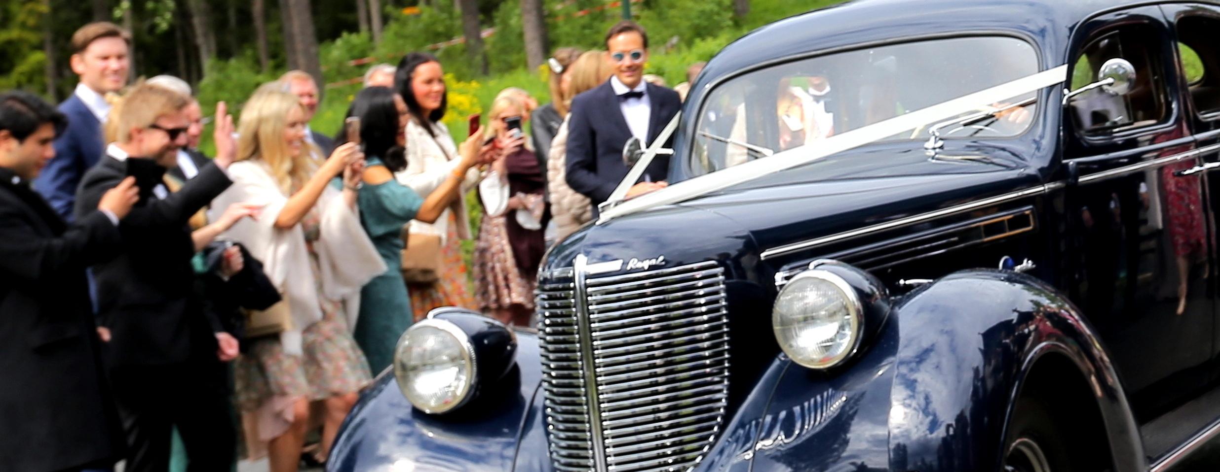 Bryllupsgjester vinker til veteranbil som har bryllupsoppdrag i Holmenkollen Oslo