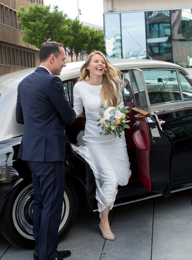 Glad brud geleides ut av bryllupsbilen. Brudgom lukker opp døren