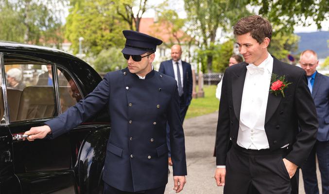 Uniformert sjåfør åpner døren på den eksklusive bryllupsbilen.