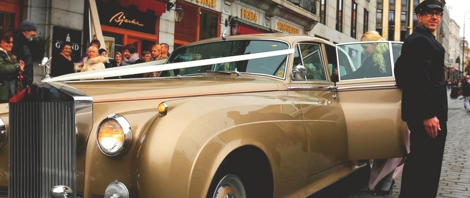 Bryllupstransporten er klar. Gullfarget Rolls-Royce med chauffeur utenfor Grand Hotel Oslo