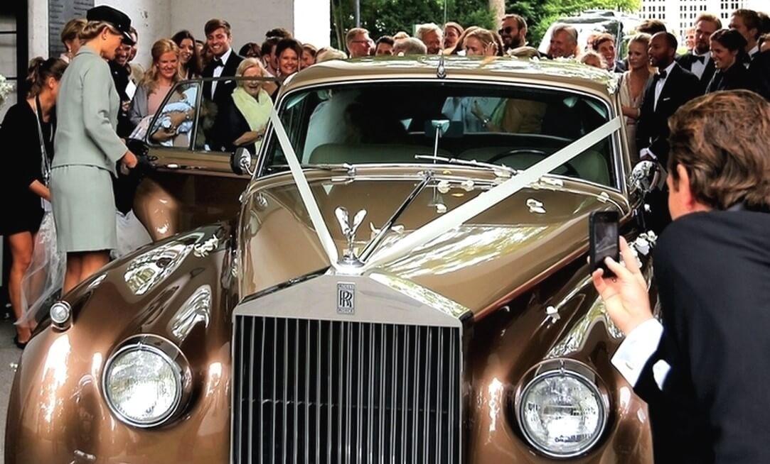 Gullfarget Rolls-Royce bryllupsbil ved Riis kirke Oslo. Chauffeur ordner klart for bryllupstransport og gjestene applauderer