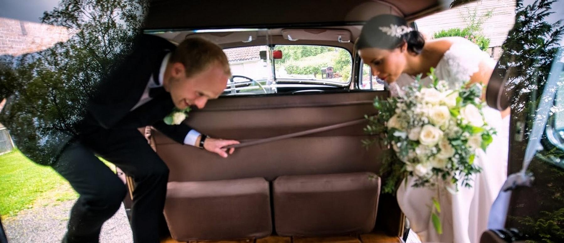 Brudepar tar plass inne i den flotte gamle bryllupsbilen