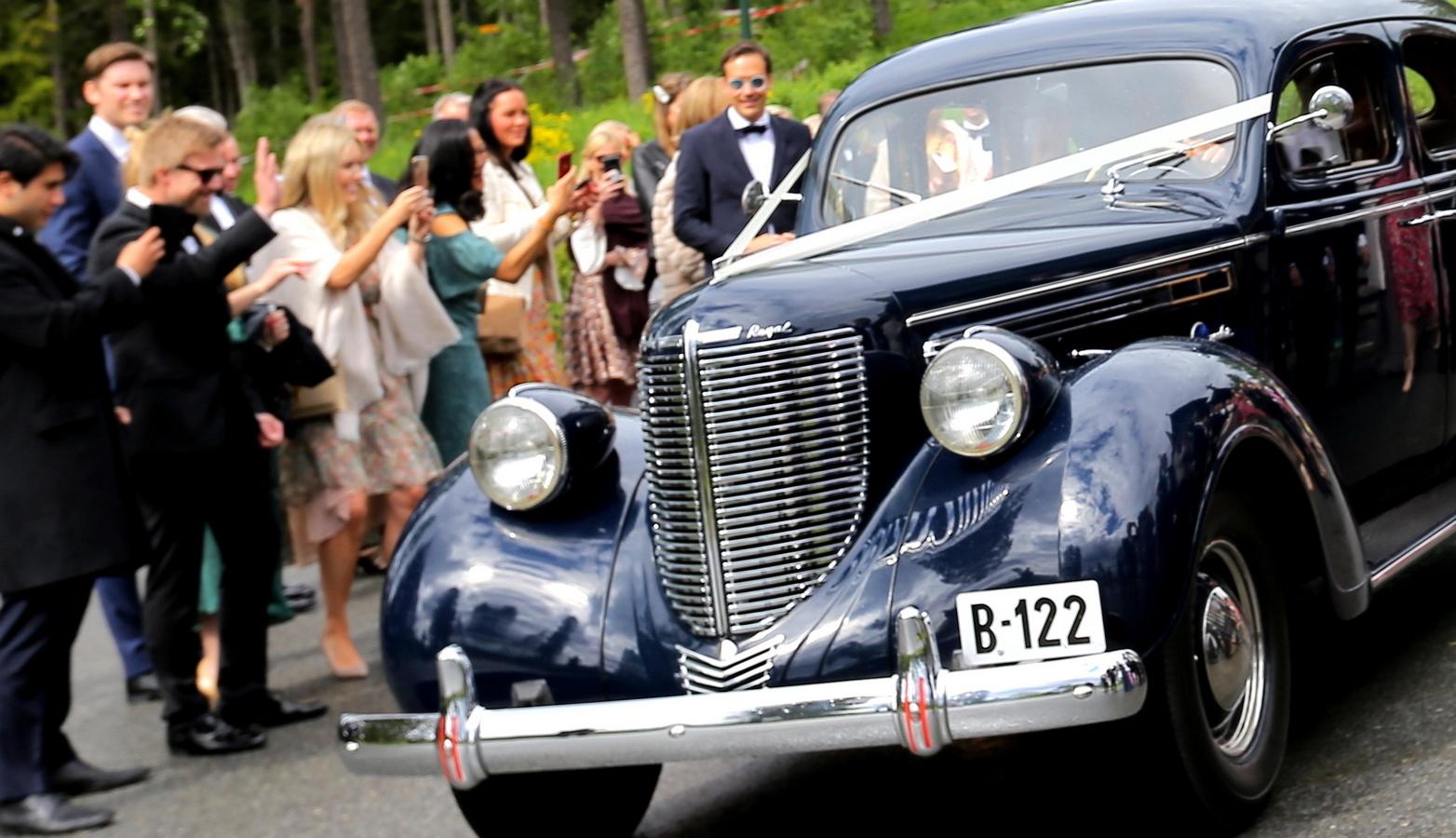 Bryllupsgjester vinker til veteranbil som tar avreise fra vielse i Holmenkollen