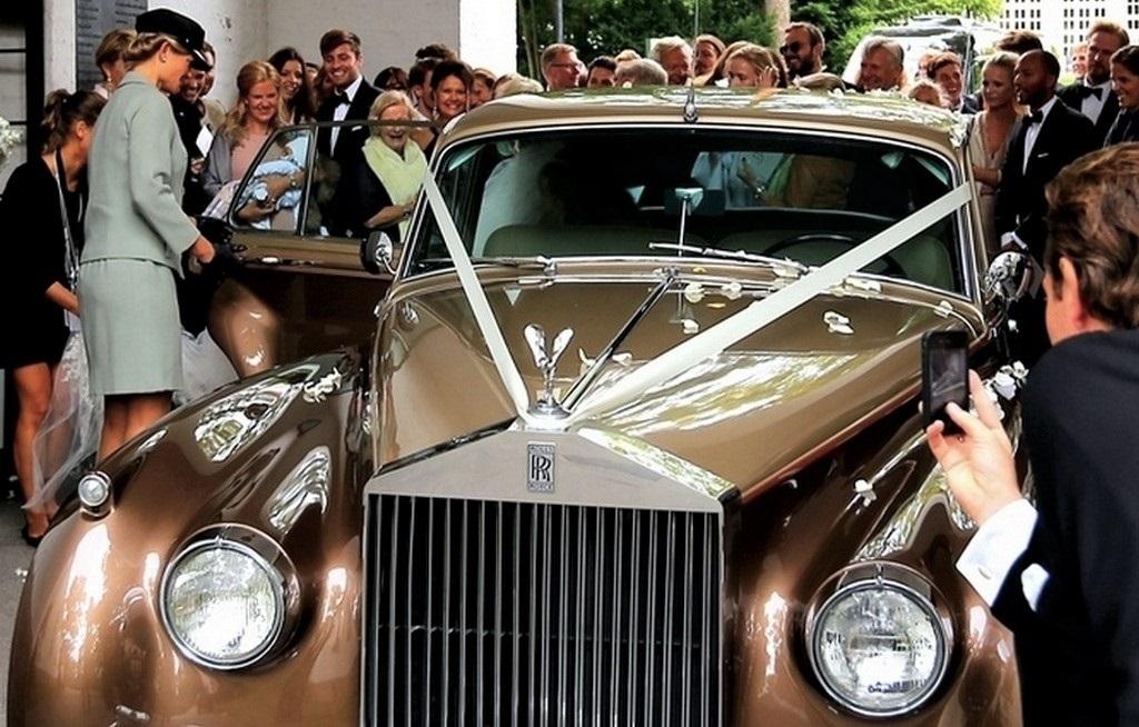 Gullfarget Silver Cloud leid ut til bryllup fra Riis kirke. Sjåfør hjelper brud mens masse gjester hyller brudeparet.