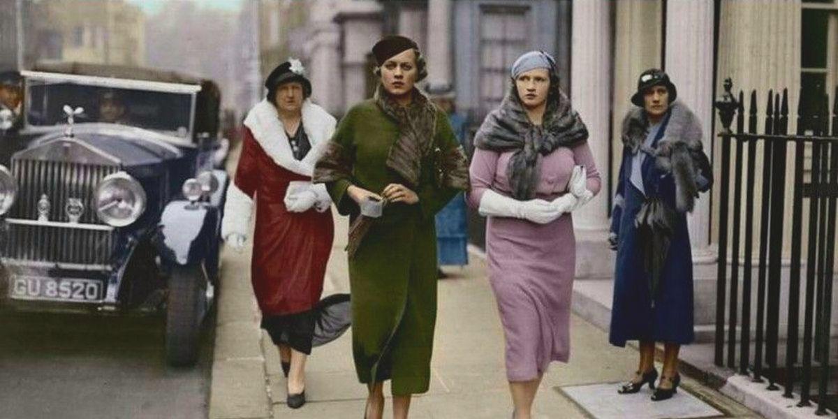 Historisk bilde med fasjonable kvinner, transportert av luksusbilen i bakgrunnen